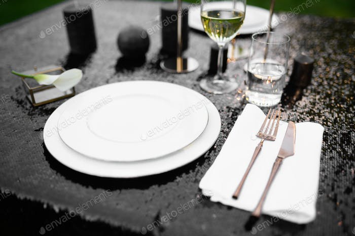 Table setting, glasses, candles and plate on black