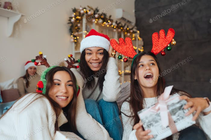 Multiethnic group of friends in Santa hats with gifts in hands