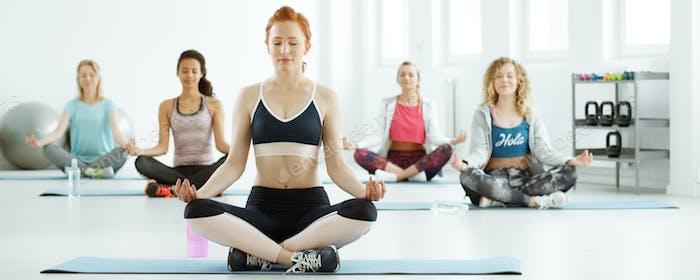 Women meditating during fitness classes