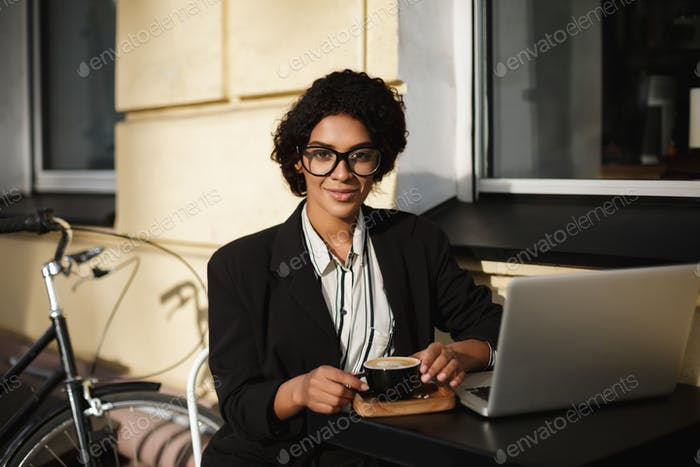 African American girl in glasses sitting at the table of cafe with laptop and cup of coffee