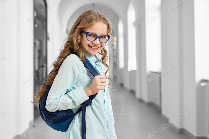 Pretty little girl with backpack standing in corridor