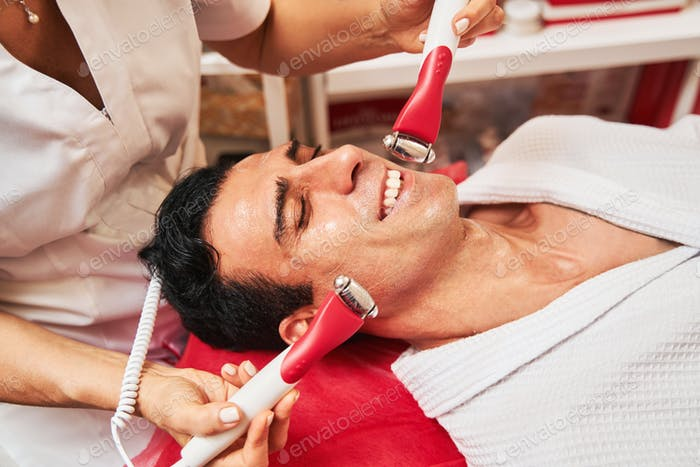 Man enjoying electric stimulation procedure in spa