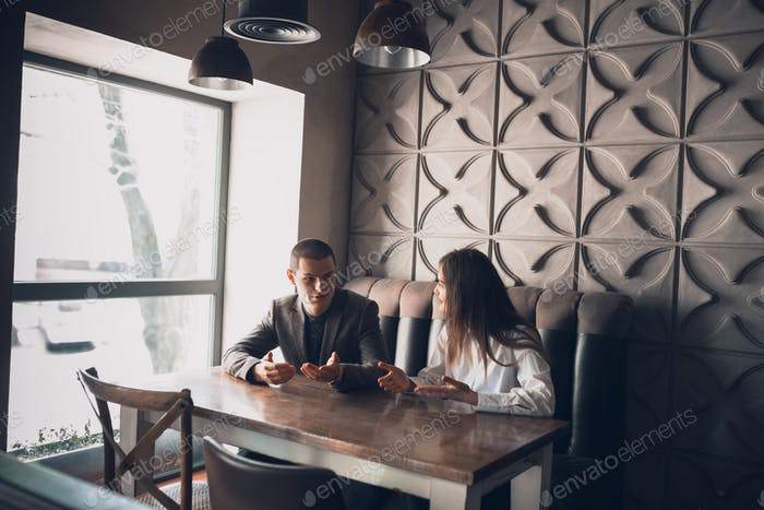 Cheerful man and woman talking, discussing at the coffee shop, cafe