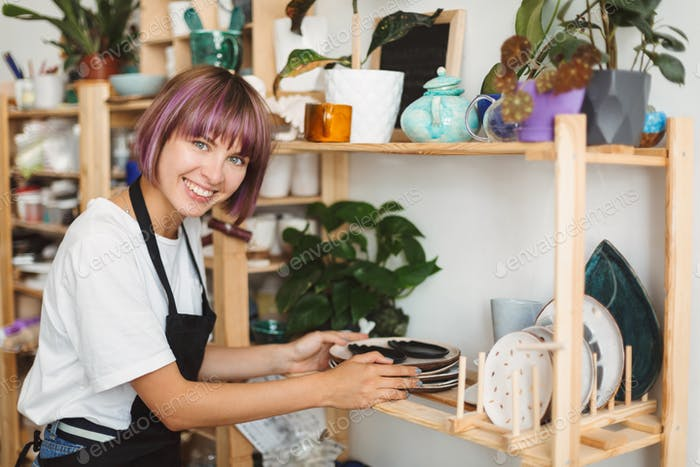 Cheerful girl with colorful hair in black apron and white T-shirt putting handmade plates on shelf
