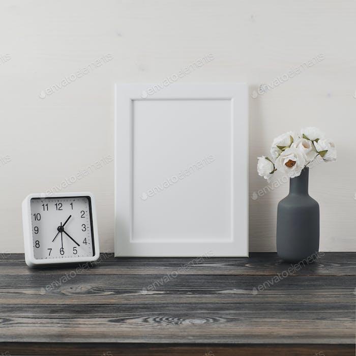 White frame, flower in vaze, clock