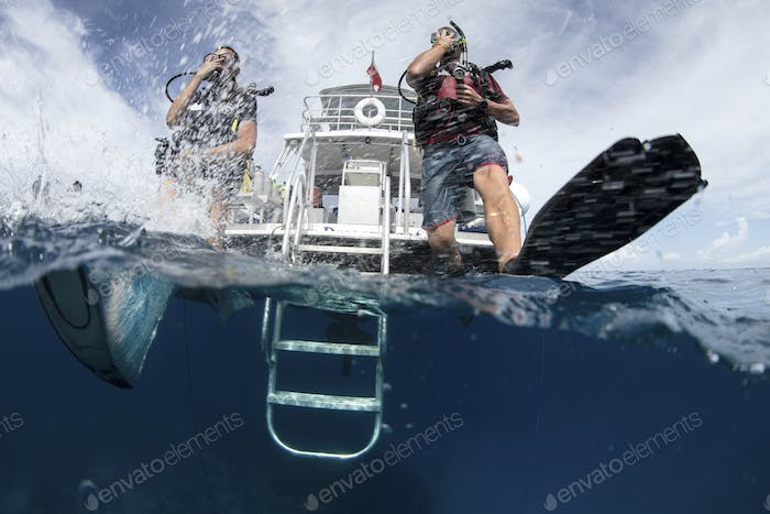 Scuba divers enter water taking a giant stride.