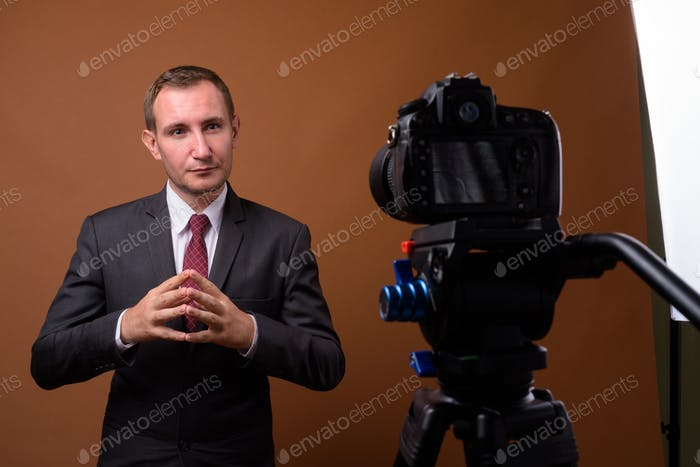 Studio shot of businessman against brown background