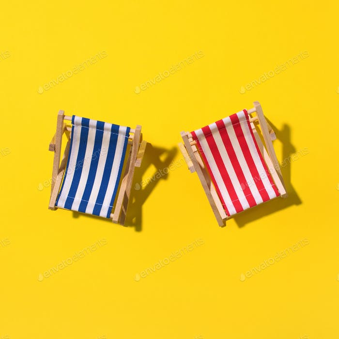 Two deck chairs with hard shadow, monstera and palm leaves on yellow paper background. Flat lay and