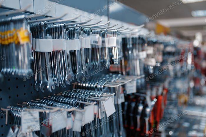 Wrenches on racks in tool store closeup, nobody