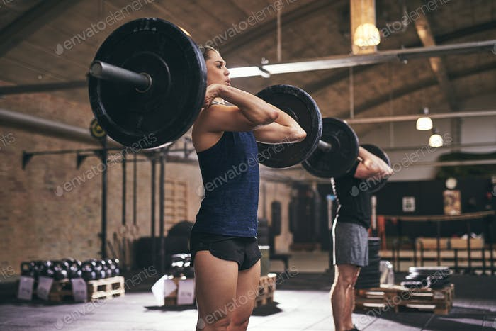 Sportive people standing with barbells on shoulders