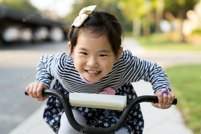 Cute little girl learning ride a bicycle with no helmet