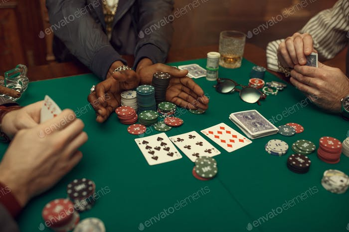 Poker players hands, gaming table on background