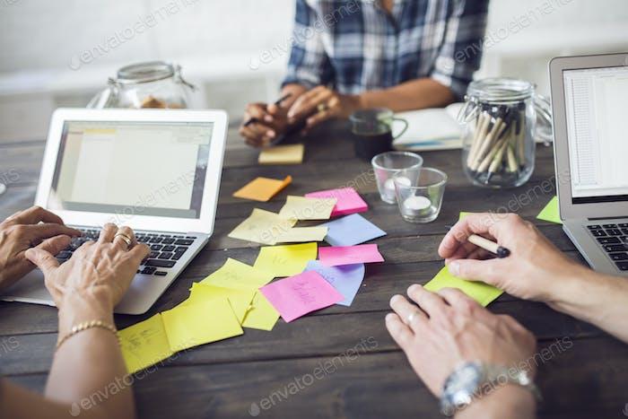 Drei Mitarbeiter arbeiten mit Laptop und Post-it Notizen