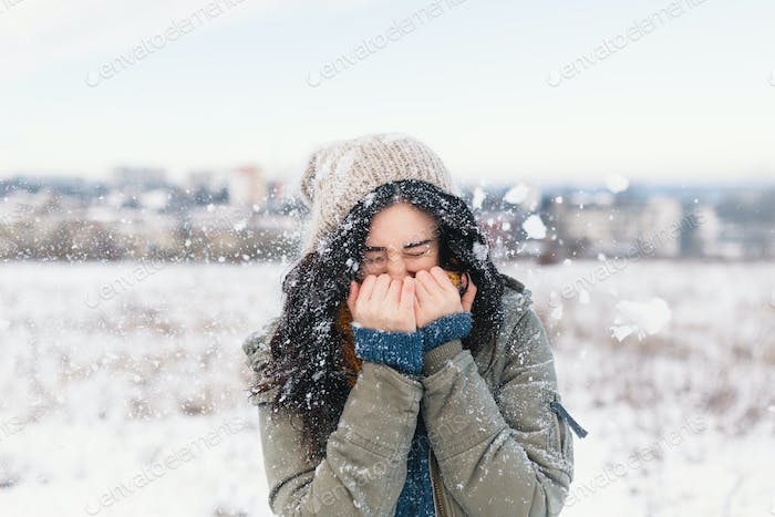 Smiling woman feeling cold snowflakes on her face during a snow