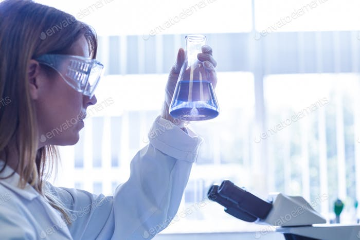 Scientist holding up beaker of chemical at the university