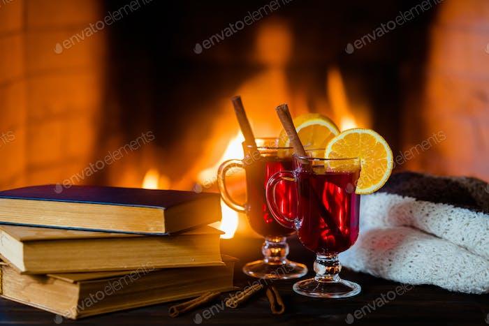 Heißer Glühwein und ein Buch auf dem Tisch. Kamin mit Feuer auf dem Hintergrund.