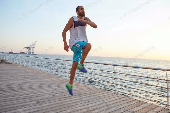 bearded jumping guy doing morning exercises by the sea