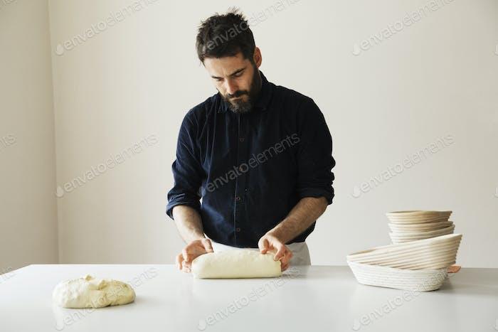 Baker steht an einem Tisch und formt Brotteig, einen Stapel Rattan-Proofing Körbe.