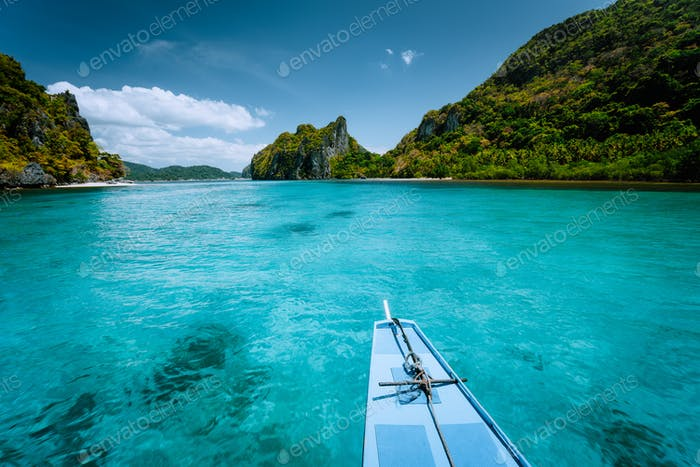 Boat trip to tropical islands El Nido, Palawan, Philippines. Steep green mountains and blue water