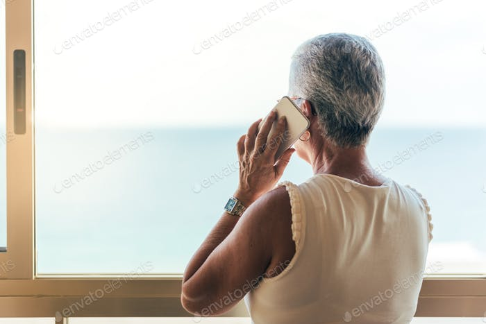 Elderly woman on the mobile phone at home