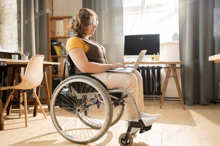 Side view of disable businesswoman in casualwear typing on laptop keypad