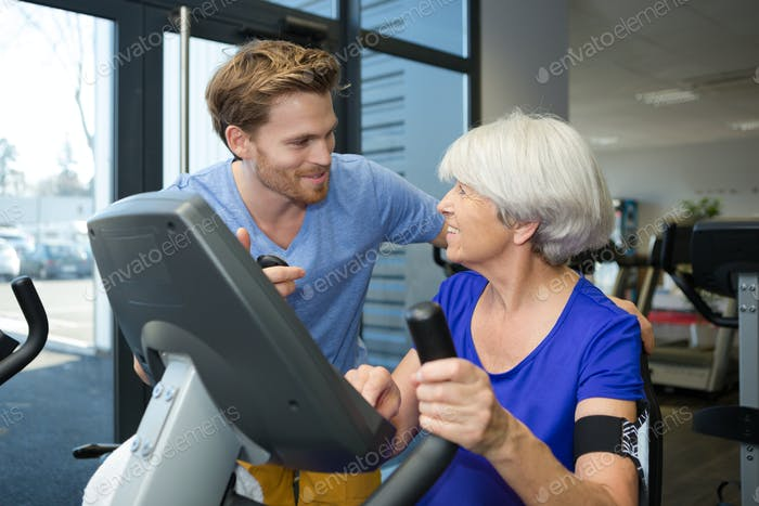 physiotherapist with senior woman using exercise machine