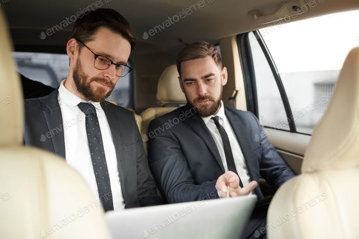 Business partners working in the car