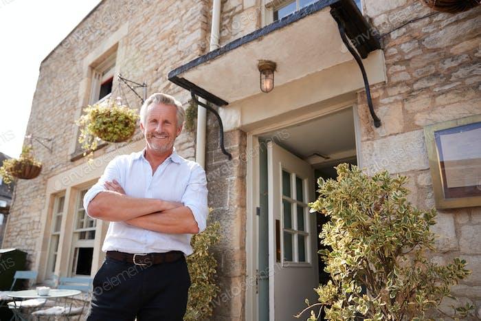 Senior male restaurant pub owner stands outside the entrance