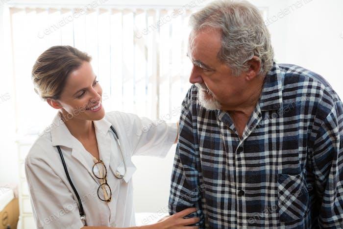 female doctor assisting senior man in walking at nursing home