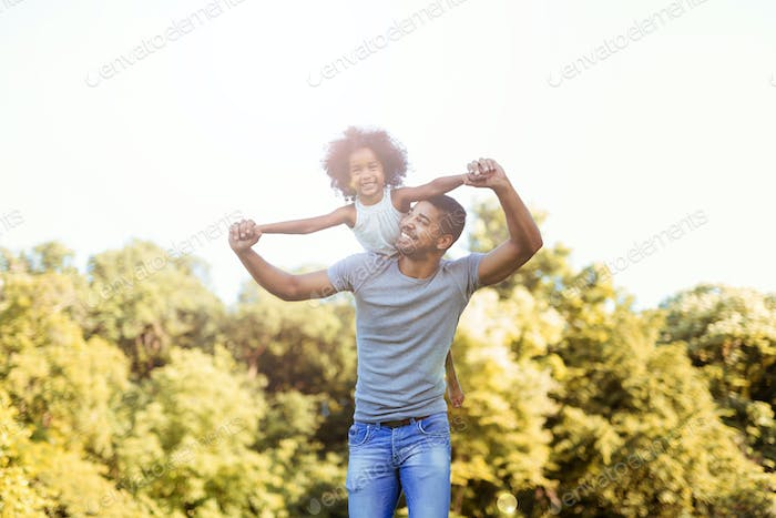 Portrait of young father carrying his daughter on his back