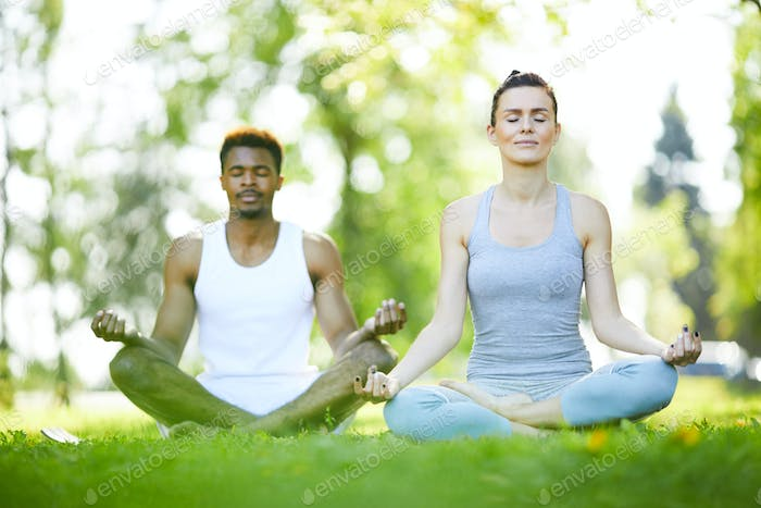 Young man and woman practicing yoga outdoors