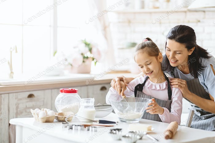 Happy mother and daughter making dough in kitchen together