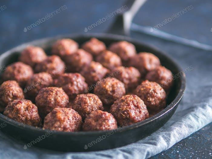 Homemade beef meatballs in cast-iron skillet
