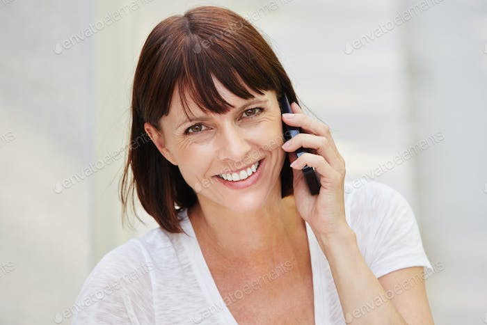 Happy older woman holding mobile phone on call