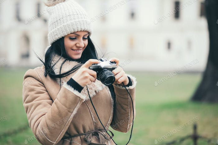 Female photographer taking pictures outdoors with a vintage camera