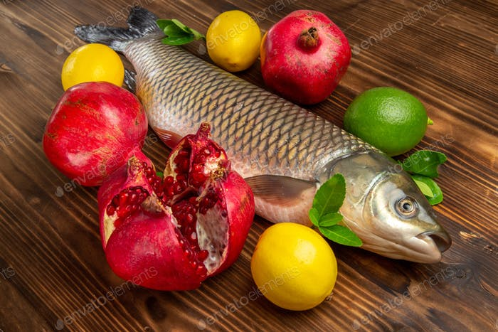 front view fresh fish with lemon and pomegranates on wooden desk ocean sea food seafood