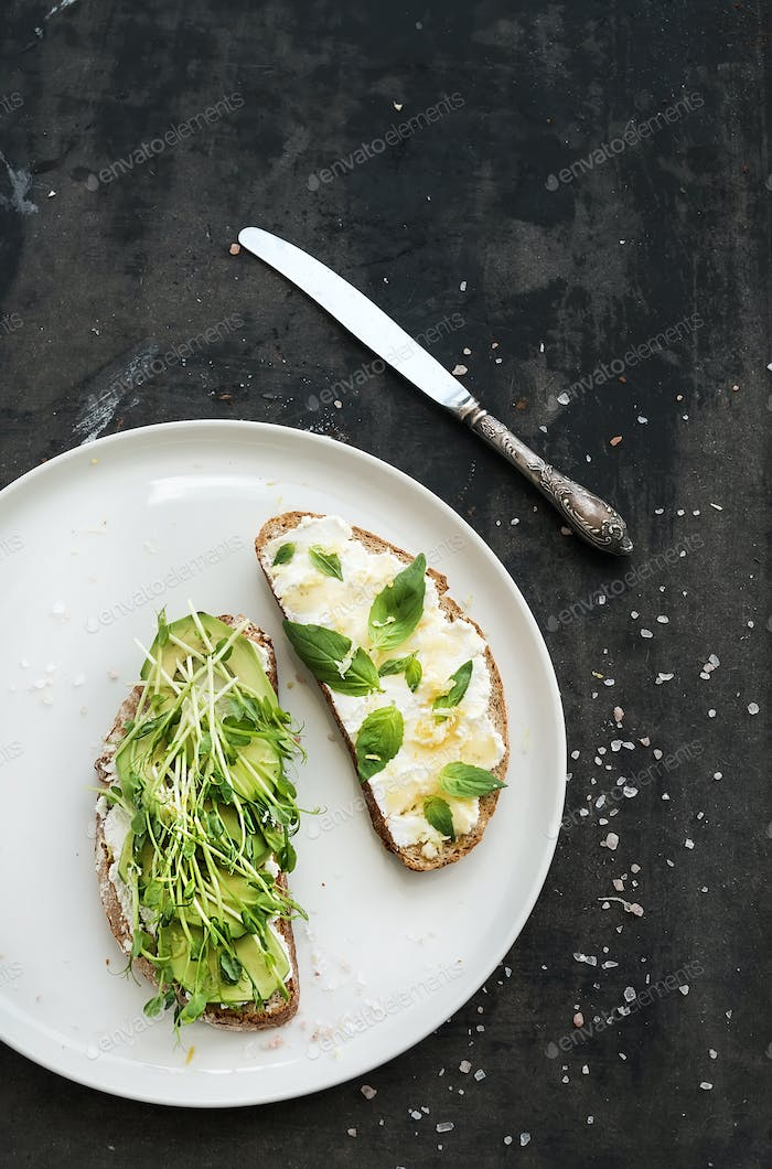 Avocado, ricotta, basil and sprout sandwiches on white ceramic plate