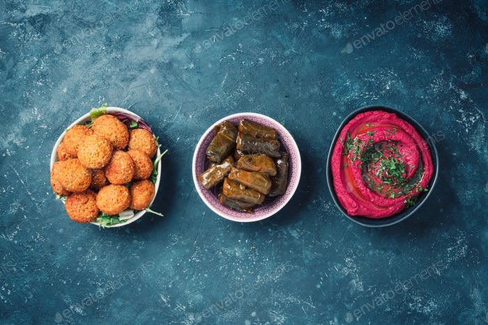 Arabic traditional cuisine. Middle Eastern meze with pita, olives, colorful hummus, falafel, stuffed