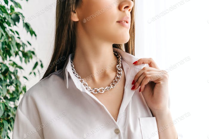 Silberne Bijouterie-Kette am Hals der Frau.