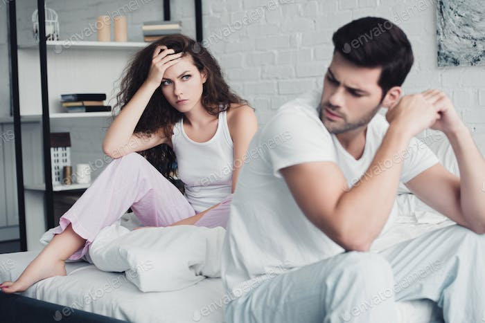 upset young couple sitting on bed, relationship difficulties concept