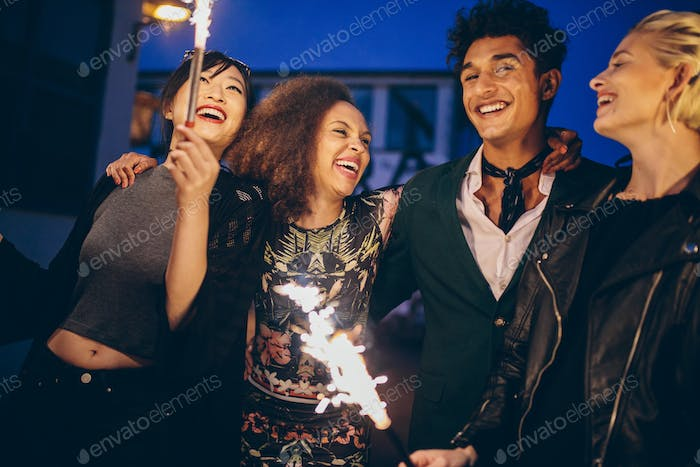 Young man and women in city at night with fireworks