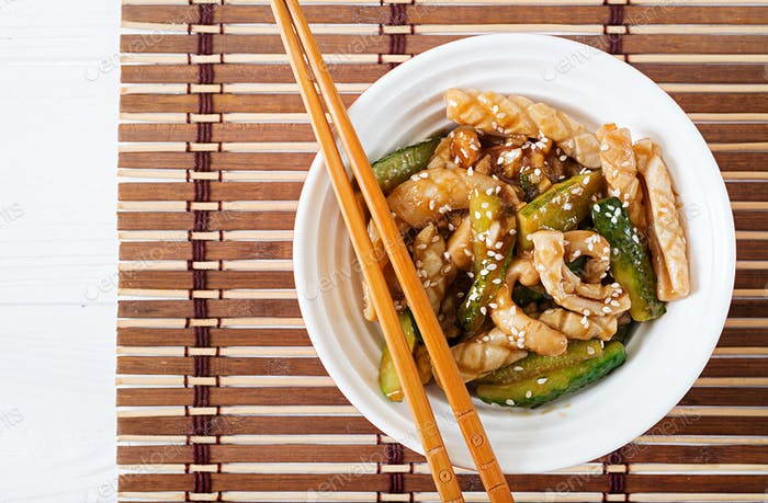 Thai spicy salad with squid and cucumber in sweet and sour sauce. Asian food. Top view.
