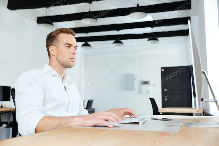 Businessman sitting and working with computer at workplace