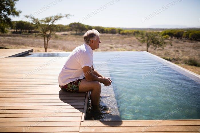 Thoughtful man sitting near pool side