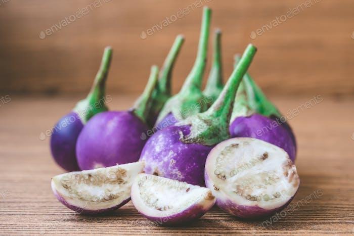 Fresh Purple eggplants on wooden table.