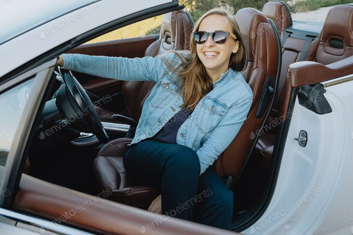 Portrait of woman in sunglasses sitting in a car