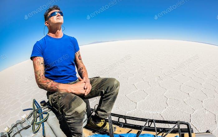 Young man solo traveler taking relax break at Salar de Uyuni saltflats