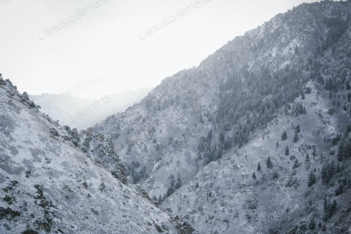 A mountain landscape, snow covered slopes reaching down into the valley.
