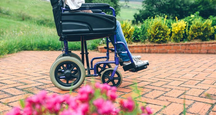 Unrecognizable elderly woman in a wheelchair