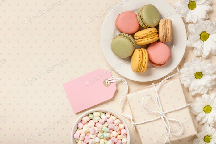 French colorful macaroons, marshmallows, git box and flowers